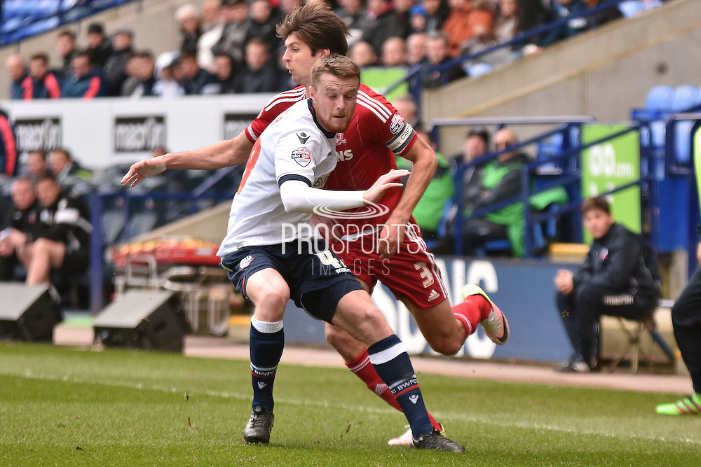 Middlesbrough Defender, George Friend is tackled by Bolton Wanderers Defender Niall Maher during the Sky Bet Championship match between Bolton Wanderers and Middlesbrough at the Macron Stadium, Bolton, England on 16 April 2016. Photo by Mark Pollitt.