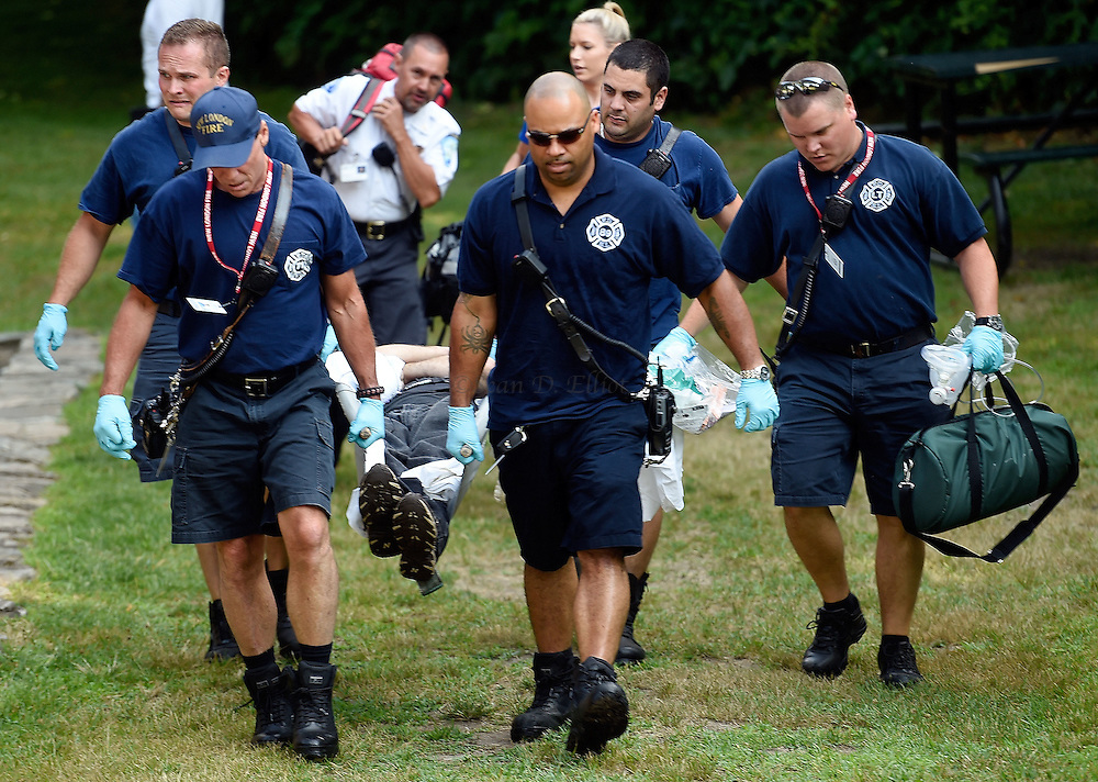 7/7/16 :: NEWS :: STAFF :: New London first responders carry the victim of an apparent overdose on the grounds of the Old Towne Mill on Mill St. to a waiting ambulance Thursday, July 7, 2016. (Sean D. Elliot/The Day)