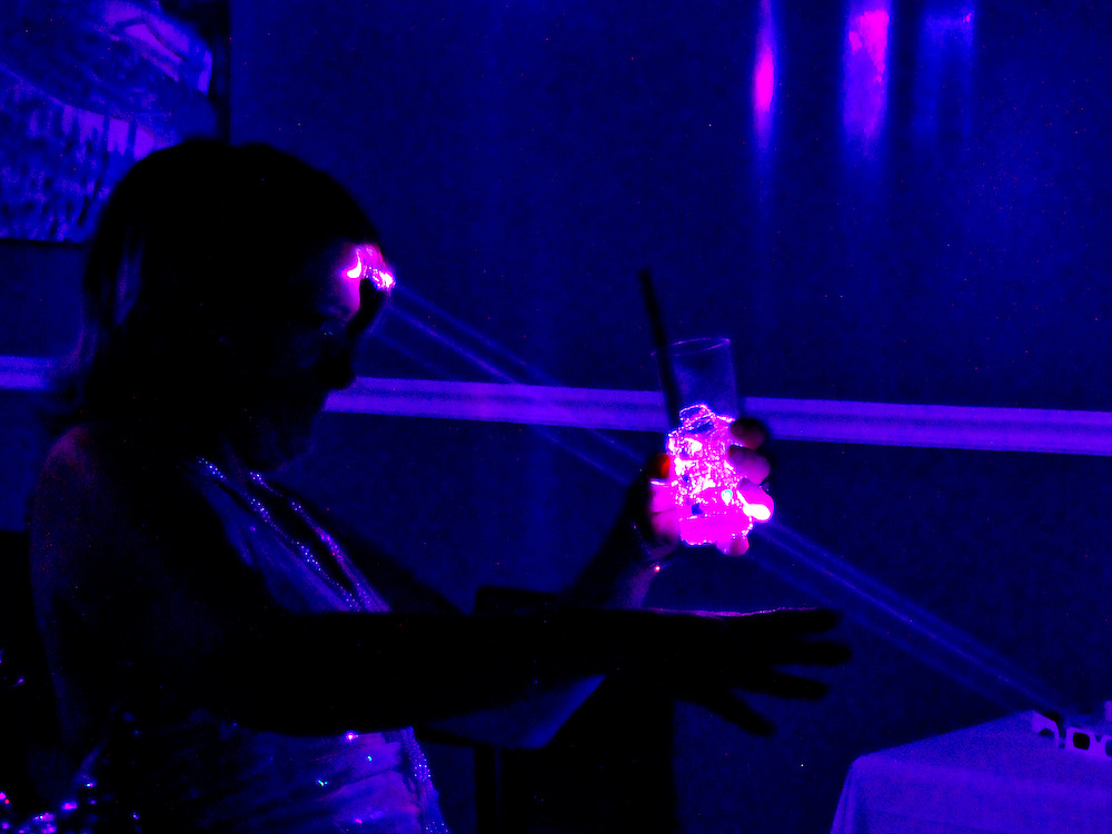 laser lights pass through and illuminate ice cubes before striking a party-goer on the forehead.