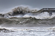 Enormous waves are smashing in to the bridge in a winter storm