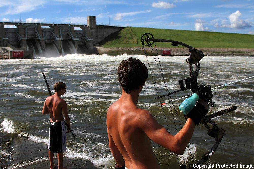 Tanner Wharton, left, and McKinnon Bell, both from Indianola, fish with bows and arrows east of the Red Rock dam where water gushes through into the Des Moines River.  A good weekend catch is about 20 fish, which Wharton, the more experienced of the pair, had pulled in by Sunday afternoon.  The boys had been fishing since Friday.  photo by david peterson