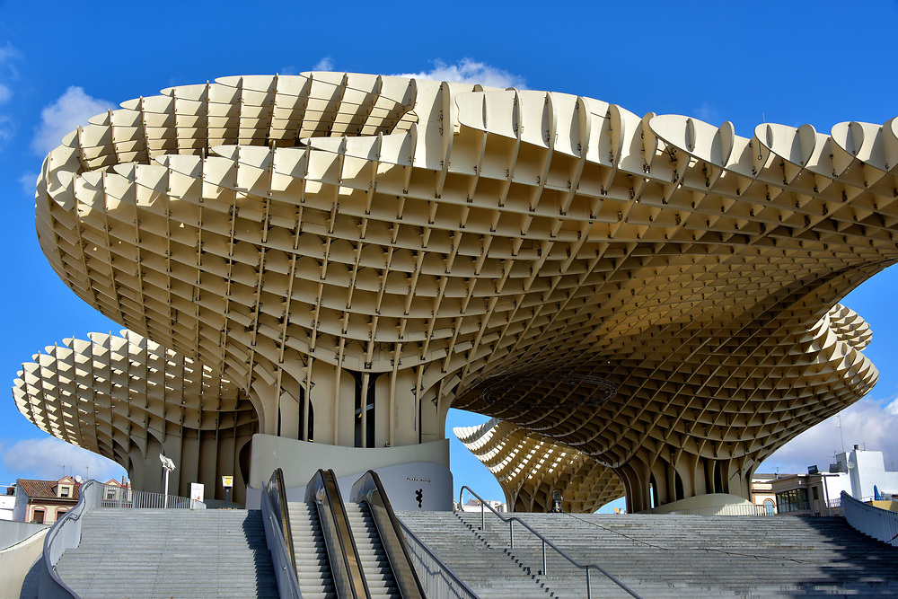 Metropol Parasol in Seville, Spain<br /> The most curious structure in Seville was built at La Encarnaci&oacute;n Square in 2011. Architect J&uuml;rgen Mayer named his creation Metropol Parasol. The locals call it Las Setas de la Encarnaci&oacute;n meaning Incarnation&rsquo;s Mushroom. The world&rsquo;s largest wooden structure measures 490 by 230 feet and 85 feet tall. In the basement are Roman and Moor artifacts. Surrounding the street level are restaurants and shops. The other two levels host staged performances, a restaurant and an observation deck. This oddity is worth seeing.