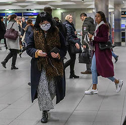 © Licensed to London News Pictures. 03/03/2020. London, UK. A tube passenger at Victoria Station in a protective mask as Boris Johnson announces his Battle Plan in Downing Street for combating the Coronavirus crisis. Photo credit: Alex Lentati/LNP
