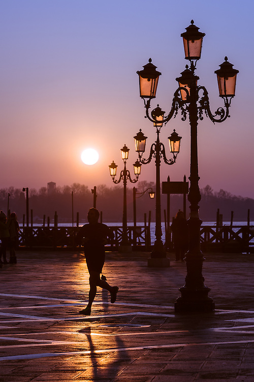 A jogger is seen running in st mark's square in venice at sunrise