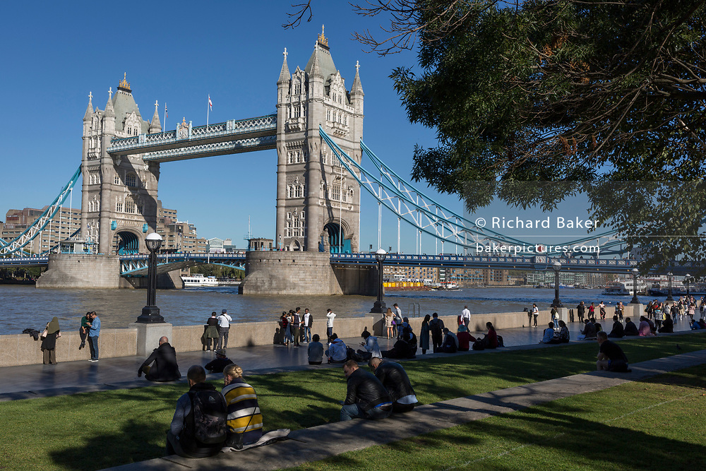 Riverside visitors walk along the Southbank beneath Tower Bridge on the river Thames, on 26th September 2018, in London, England.