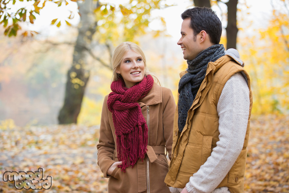 Happy woman looking at man during autumn