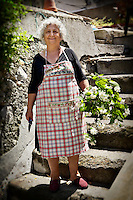 Elderly Italian woman in a garden with flowers, Amalfi, Italy.