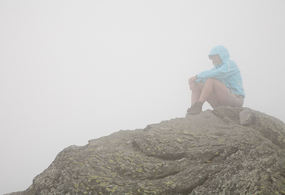 A hiker sits in the fog on top of Camel's Hump in Vermont
