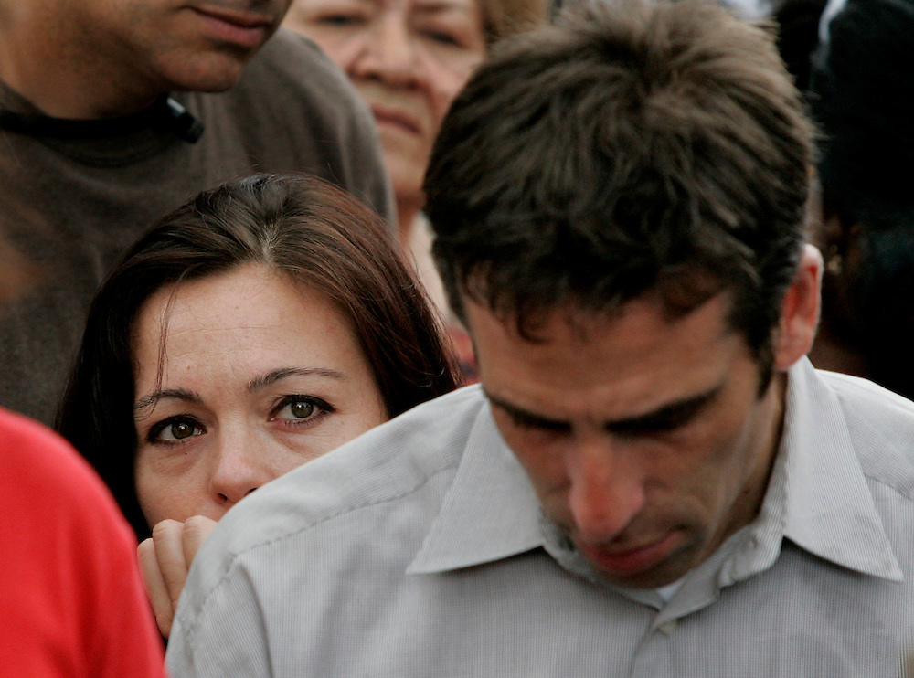 Suzanne Vitadamo (C), sister of Terri Schiavo, tries to hold in her tears during easter mass as her brother Bob Schindler, Jr. (R) prays outside of the Woodside Hospice in Pinellas Park, Florida  on March 27, 2005. REUTERS/Scott Audette