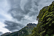 Dramatic clouds swirl over Siberia Valley. The Gillespie Pass Circuit follows the Young and Wilkin Rivers in Mount Aspiring National Park, in the Southern Alps. Makarora, Otago region, South Island of New Zealand.