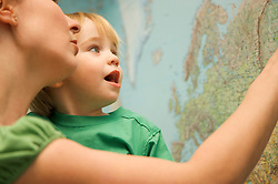 Mother holding toddler looking at world map