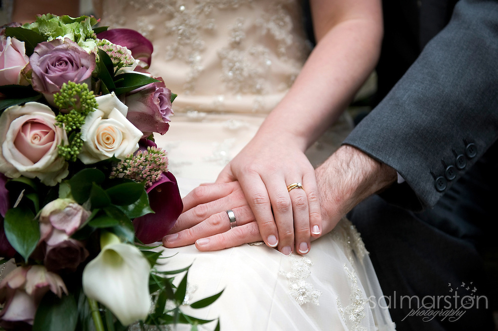 Detail shot of wedding couple holding hands featuring the rings and bridal bouquet of muted roses and kala lillies
