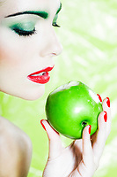 beautiful caucasian woman portrait eating an apple studio on green background