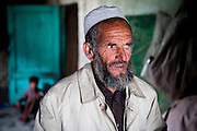 Kabul: 65 year old Khalil Rahman at his makeshift home at Tamil Mill Bus site in Kabul city. Khalil and his family returned to Afghanistan in 2002 from Punjab in Pakistan where they worked at a brick factory...He lost his right eye during the Russian invasion in the late 1980's...Tajik and Pashtun families live side by side without any major conflict at the Tamil Mill Bus site. Over 70% of the families are returnees from the period 2002-2004 who are unable to achieve sustainable reintegration in their places of origin and subsequently drifted to Kabul City in search of work...There is a nearby school which is accessible to the children but the poor economic circumstances of the many families oblige them to send their children out to work. low levels of literacy, particularly amongst the women, limit their access to employment other than the lowest paid daily wage labor...Afghanistan. /UNHCR/Jason Tanner/February 2011