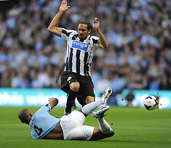 Manchester City's Vincent Kompany tackles Newcastle United's Jonas Gutierrez  - Photo mandatory by-line: Joe Meredith/JMP - Tel: Mobile: 07966 386802 19/08/2013 - SPORT - FOOTBALL - Etihad Stadium - Manchester - Manchester City V Newcastle United - Barclays Premier League