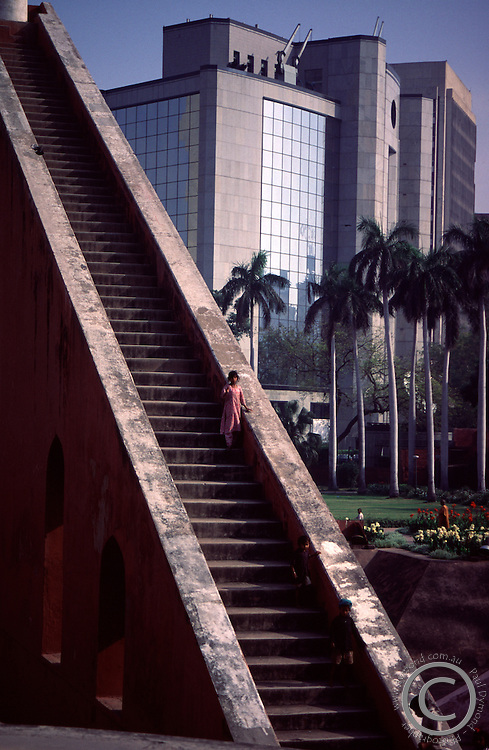 A young girl on the steps of a giant astronomical measuring device at Jantar Mantar in the heart of New Delhi, India.