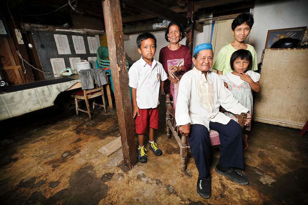 Bapak Mustari Lotong with his wife, Ibu Kagau, daughter and grandchildren, Jongaya leprosy settlement, Makassar, Sulawesi, Indonesia. Bapak Mustari Lotong, around 70 years old, is a Rukun Warga in Jongaya leprosy settlement - he works for and represents the community.  He found out he had leprosy around the age of 10 and moved to the settlement shortly after.  His wife, Ibu Kagau, 57, discovered she had leprosy when she was 9 years old and came to Jongaya a year later.  Both are originally from Sulawesi.  They met at Jongaya and married in 1970 after Bapak Mustari's first wife died.  Bapak has 7 children and 5 grandchildren from his marriage to Ibu Kagau, and another 7 children from his first marriage.  None of his children or grandchildren have leprosy.
