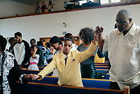 &quot;America in the Middle&quot; is a collection of images showing communities and individuals personally affected by policies but often-overlooked by politicians. |||<br /> <br /> Dressed in his Easter Sunday best, Omarion Johnson, 12, holds hands with his great grandmother Katrina Jiles and Edward Crisp, a mentor, during service at Antioch Baptist in East Chicago, Indiana. The community recently learned of lead poisoning in its water and soil.<br /> <br /> Chicago Freelance Photographer | Alyssa Schukar | Photojournalist