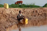 Claudette aged 7 collecting water from the Akagera river near Kajevuba Village. Juru Sector. Bugesera district. Rwanda. Water Aid/UK