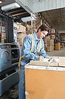 Man making notes in distribution warehouse