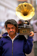 ECUADOR, HIGHLANDS, CUENCA man with a gramophone on street