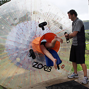 Participants enter a Zorb Globe preparing for  a ride down the hill. The sport of Zorb globe riding was invented in New Zealand and globes are designed, manufactured and tested there, The Zorb globe is an 11 foot high inflatable transparent sphere which you can ride inside. Two feet of air protect you from the ground enabling you to globe ride down hills at high.  Agrodome, Western Rd. Ngongotahaha.  Rotorua, New Zealand,, 11th December 2010 Photo Tim Clayton.