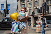On the day that covid pandemic guidelines for shoppers in England mean that the wearing of face coverings in shops is mandatory, a lady shopper carries party balloons , on 24th July 2020, in London, England.