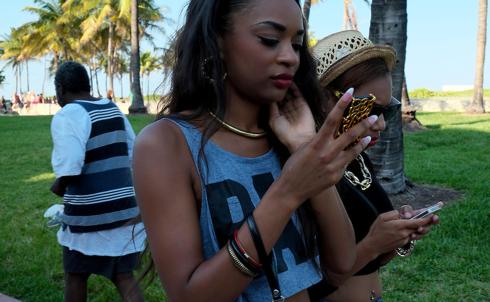 MIAMI BEACH - MAY 25: Girls looking their smartphone during the Urban Beach Weekend, on May 25, 2013 in Miami Beach. This is the largest Urban Festival in the World, that caters towards the Hip Hop Generation. Over 300.000 participants make the annual trek to South Beach for 4 days full of fun, food, festivities, entertainment, music, and more.
