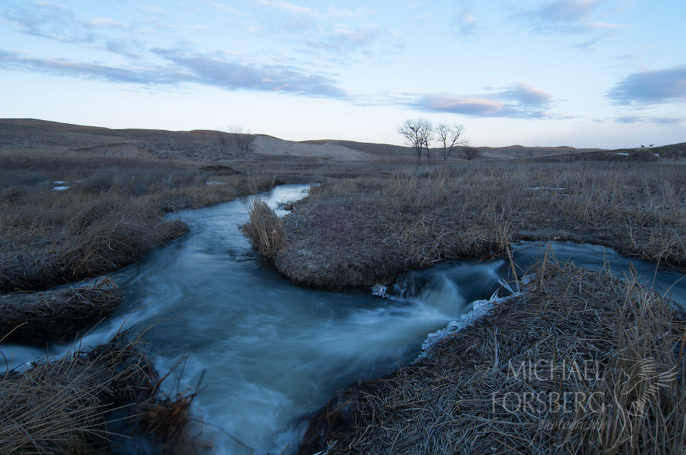 Nebraska Sandhills. Peterson Ranch.<br /> <br /> Small waterfalls along Blue Creek in winter with Mule deer on horizon<br /> <br /> Blue Creek stays open even in the deepest cold of winter, fed by powerful underground springs from the Ogallala aquifer below.
