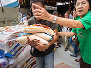 "07 AUGUST 2014 - BANGKOK, THAILAND:      A man carries sacks of rice away from a food distribution at Pek Leng Keng Mangkorn Khiew Shrine in Bangkok. Thousands of people lined up for food distribution at the Pek Leng Keng Mangkorn Khiew Shrine in the Khlong Toei section of Bangkok Thursday. Khlong Toei is one of the poorest sections of Bangkok. The seventh month of the Chinese Lunar calendar is called ""Ghost Month"" during which ghosts and spirits, including those of the deceased ancestors, come out from the lower realm. It is common for Chinese people to make merit during the month by burning ""hell money"" and presenting food to the ghosts. At Chinese temples in Thailand, it is also customary to give food to the poorer people in the community.   PHOTO BY JACK KURTZ"