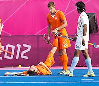 LONDEN - Sander de Wijn probeert  de met kramp kampende Robert van der Horst te helpen,maandag in de hockey wedstrijd tussen de mannen van Nederland en India tijdens de Olympische Spelen in Londen .ANP KOEN SUYK