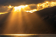 Shoots of light from the sky throught the mountaon slopes to the sea