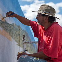 063015      Cayla Nimmo<br /> <br /> Ernest Skeet paints in the details on a mural based on historic photos on the front of Milan Town Hall Tuesday.
