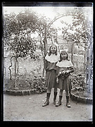 identical dressed sisters in garden France circa 1920s