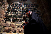 "Serbian orthodox priest kisses the wall of the memorial tower at Gazimestan, the site of the 1389 ""Battle of Kosovo""...Gazimestan, Kosovo, Serbia."
