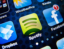 detail of iPhone 4G screen showing Spotify online music streaming  app