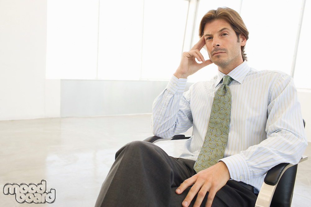 Business man sitting in chair, portrait