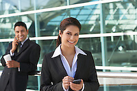 Businesswoman using PDA with businessman using mobile phone in background, outdoors