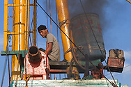 Dock worker operating a lift to load a ship with cargo at Sunda Kelapa (the old port), Jakarta, Indonesia.