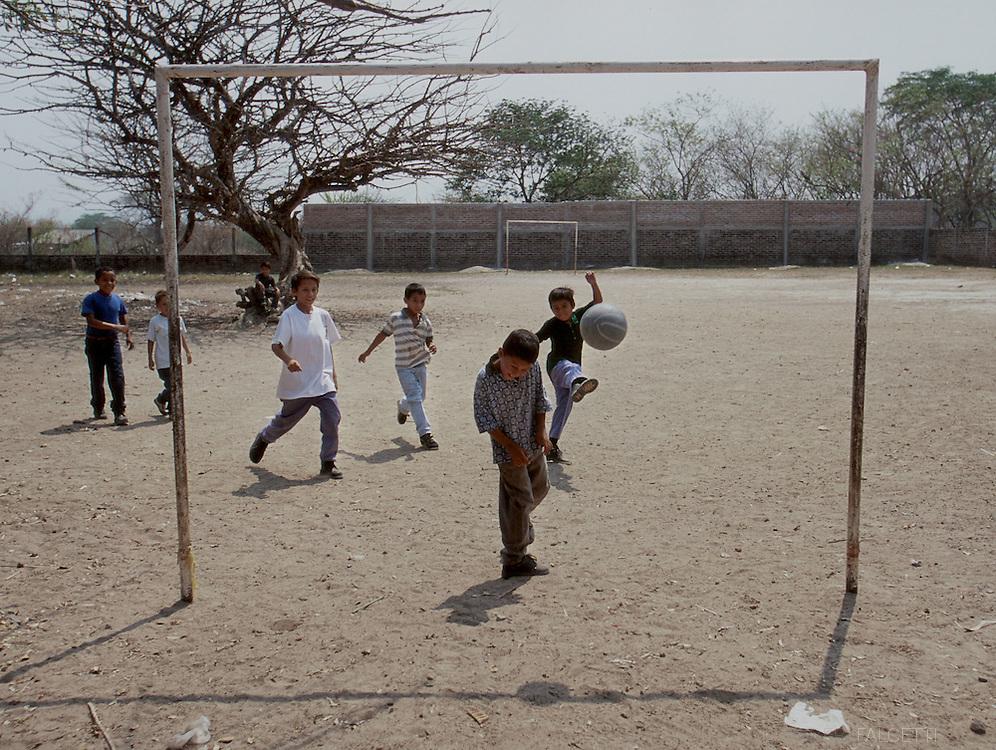 COYOLITO (Tejutla), CHALATENANGO, EL SALVADOR- MAY 2000: A group of school children play a game of futbol (soccer) in a school yard in Departamento de Chalatenango.   (Photo by Robert Falcetti). .