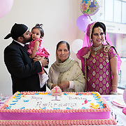 Hounslow, Greater London, UK, January 25, 2015. Sikh Temple Gurdjwara Sri Guru Singh Sobha. <br /> The Groom's grandmother (in the middle), the couple and the little Ashreena get together for cutting the cake for her 1st birthday party. Unlike what usually happens in the Indian community, where even today daughters are not celebrated, Gurmeet and her husband Sandeep decided to give a big party for wishing a happy birthday to their daughter and blessing girls in general.