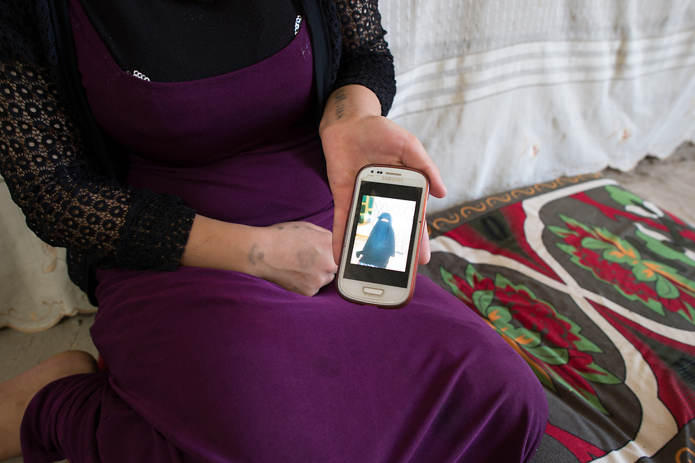 An 18-year-old Yazidi women shows on her phone a photo of herself that was taken during she was in ISIS captivity. She and her husband were taken to Ramadi in Iraqi Anbar province, where she gave birth of their son. Together with him she managed to flee captivity, but her husband, whose remain in unknow, she had to left behind. Just recently the Iraqi Kurdish government reimbursed the money her family paid for organizing her escape from ISIS. She like to go to Germany because in Iraq she gets no support, as she says. Shariya, Iraq, July 1, 2016