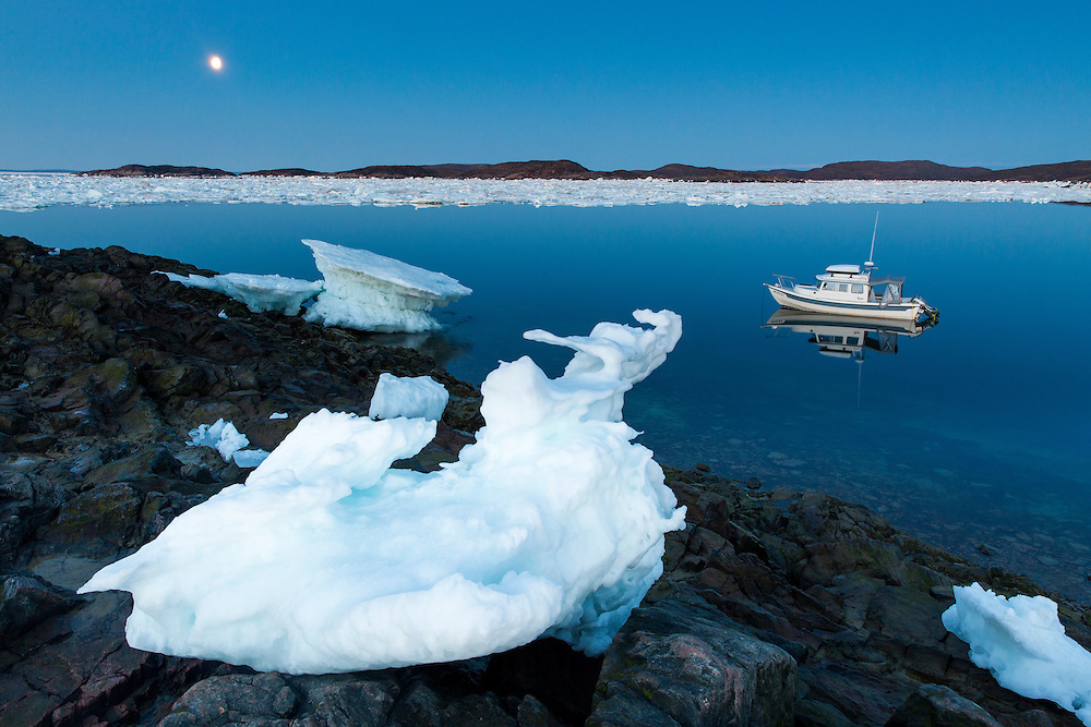 Canada, Nunavut, Territory, Full moon rises above melting iceberg and C-Dory expeditoin boat anchored along Frozen Strait in northern Hudson Bay near Arctic Circle