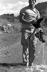 Man in a stream dumping water out of his boots after a hike