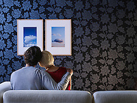 Couple sitting on sofa looking at pictures on wall back view