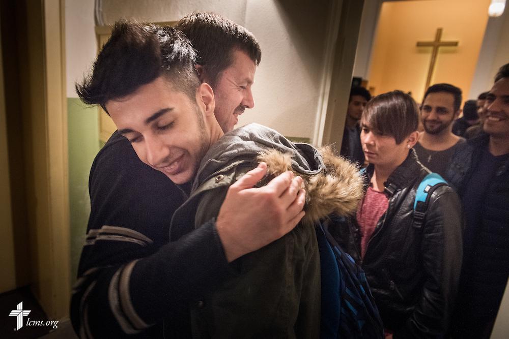 The Rev. Dr. Gottfried Martens hugs a refugee following Bible study on Saturday, Nov. 14, 2015, at the Dreieinigkeits-Gemeinde, a SELK Lutheran church in Berlin-Steglitz, Germany. LCMS Communications/Erik M. Lunsford