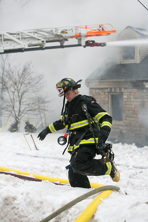 Hingham, MA 02/11/2013.A Hingham firefighter climbs over a snow bank at the scene of a 3 alarm house fire at 276 East St. in Hingham on Monday, February 11..Alex Jones / www.alexjonesphoto.com