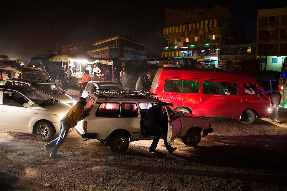 Motorists push their vehicle through a busy intersection near the slum of Dandora in Nairobi, Kenya.