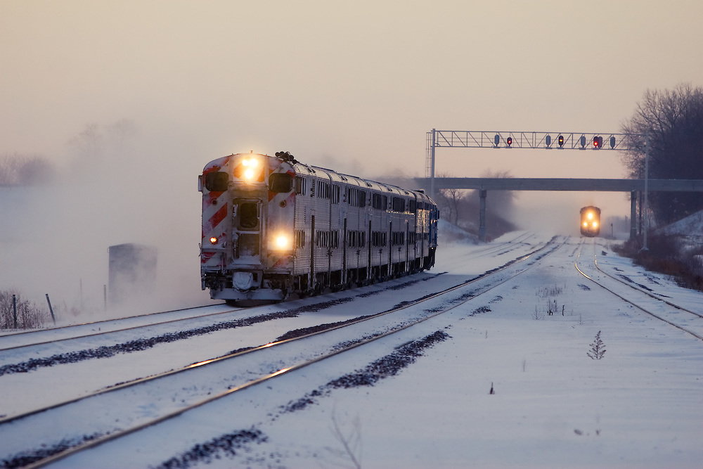 Kicking up a fresh coat of snow, a Metra train bound for downtown Chicago approaches the suburban LaFox, IL depot as a Union Pacific coal train rolls down the tracks in the distance.