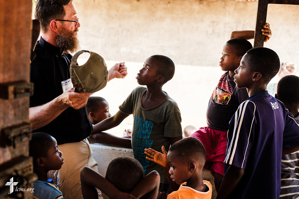The Rev. Daniel Mulholland, team chaplain and pastor of Shepherd of the Valley Lutheran Church, Fort Bridger, Wyo., teaches children about Jesus Christ on the second day of the LCMS Mercy Medical Team on Tuesday, May 8, 2018, in the Yardu village outside Koidu, Sierra Leone, West Africa. LCMS Communications/Erik M. Lunsford